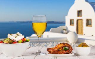 Photo d'un déjeuner grec face à la mer: salade grecque avec fêta, verre de vin et poulpe cuisiné